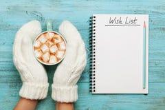 在手套的妇女手拿着杯子热的可可粉或巧克力用蛋白软糖和笔记本有愿望的在绿松石葡萄酒桌上 免版税库存照片