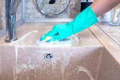 在手套的妇女的手清洗厨房水槽 图库摄影