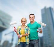 在手套的微笑的夫妇与漆滚筒 免版税库存照片