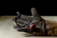 在手套的手与为工作的工具在车间 被保护的手  库存图片