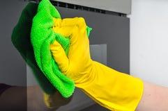 在手套的手与抹微波炉的绿色旧布 免版税库存照片
