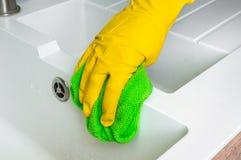 在手套的手与绿色旧布在厨房里抹水槽 库存图片