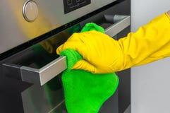 在手套的手与绿色旧布在厨房里抹烤箱 免版税图库摄影