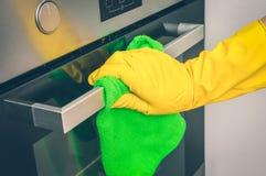 在手套的手与绿色旧布在厨房里抹烤箱 免版税库存照片