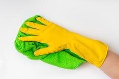 在手套的手与绿色旧布在厨房里抹白色门 免版税图库摄影