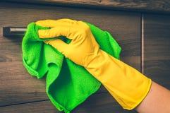 在手套的手与绿色旧布清洗不锈钢把柄 库存照片