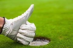 在手套高尔夫球的人的手在孔附近显示好 免版税库存照片