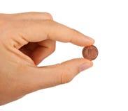 在手指之间的1欧分 库存照片