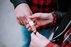 在手指关闭的白色杀菌膏药 免版税图库摄影