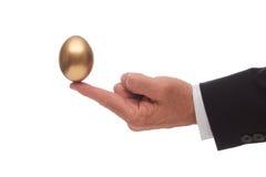 在手指平衡的金黄鸡蛋 免版税库存图片