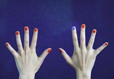 在手指的一种不同钉子颜色在白种人手上 红色和蓝色被绘的指甲盖 图库摄影