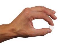 在手指的人的手举行一药片 免版税库存图片