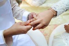 在手指的妇女金黄圆环 免版税库存图片