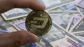 在手指的手拿着在背景的一个金币破折号与美元票据  股票视频