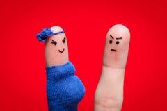 在手指绘的面孔 因为妇女怀孕,人生气 免版税库存图片