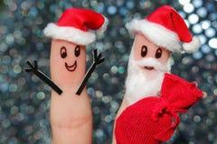 在手指绘的面孔 圣诞老人给礼物 免版税库存图片