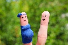 在手指绘的面孔 愉快的夫妇,妇女怀孕 库存图片