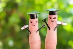 在手指绘的面孔 拿着他们的文凭的学生在毕业以后 图库摄影