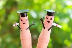 在手指绘的面孔 拿着他们的文凭的学生在毕业以后 库存照片