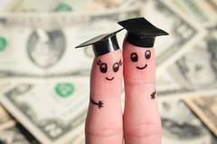 在手指绘的面孔 拿着他们的文凭的学生在美元背景的毕业以后  免版税图库摄影