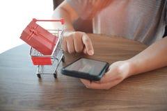 在手推车的红色礼物盒有使用手机的妇女的 对网络购物概念 免版税库存照片