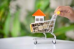 在手推车的议院和金钱硬币,买卖不动产 物产投资和房子抵押财政概念 库存图片