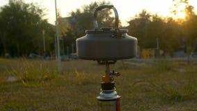 在手提油炉的水壶热化在公园 股票录像