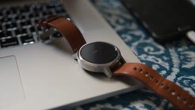 在手提电脑的聪明的手表皮革在书桌智能手机 库存照片