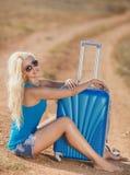 在手提箱的白肤金发的开会在路的边 免版税库存图片