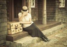 在手提箱附近的困厄的20世纪20年代女孩在与葡萄酒Effec的门廊 库存图片