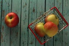 在手提篮的苹果在木背景 免版税库存图片