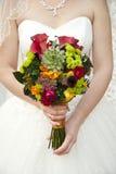 在手新娘的美丽的婚礼花束 免版税库存图片