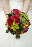 在手新娘的美丽的婚礼花束 免版税库存照片