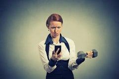 在手机举的哑铃的恼怒的女商人读书新闻电子邮件 图库摄影