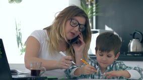 在手机和做的多任务母亲谈话在儿子附近注意坐厨房 股票视频