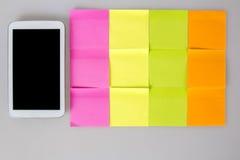 在手机旁边的便条纸五颜六色的空白 免版税库存图片