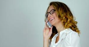 在手机白种人女性模型的特写镜头画象快乐的女孩谈话在白色背景在演播室 股票视频