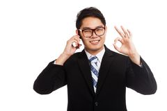 在手机的亚洲商人微笑展示OK标志谈话 免版税库存图片