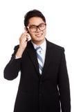 在手机的亚洲商人微笑谈话 库存照片