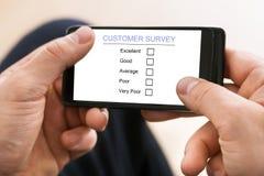 在手机的人填装的消费者调查形式 免版税库存照片