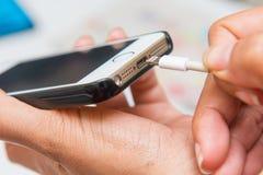 在手机的充电的电池 免版税库存照片