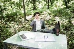 在手机的商人谈话在办公室桌上在有腿的绿色森林里在桌上 到达天空的企业概念金黄回归键所有权 免版税库存照片