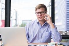 在手机的商人谈话在办公室 在sm的年轻人电话 库存照片