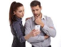 在手机的夫妇和秘密消息 免版税库存照片