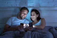 在手机的夫妇在后床上在享受人脉、比赛和互联网连接的晚上 库存图片