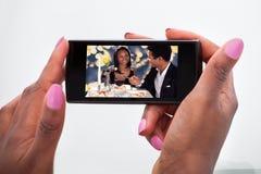 在手机的妇女观看的录影在家 库存图片