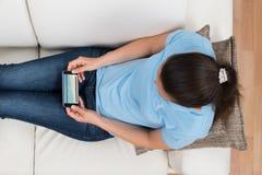 在手机的妇女观看的录影 免版税库存图片