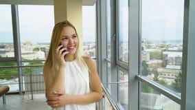 在手机的年轻女人谈话在有都市风景的宽敞的房间在背景 影视素材