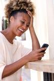 在手机的微笑的非裔美国人的妇女读书正文消息户外 库存照片