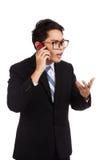 在手机的恼怒的亚洲商人谈话 免版税库存图片